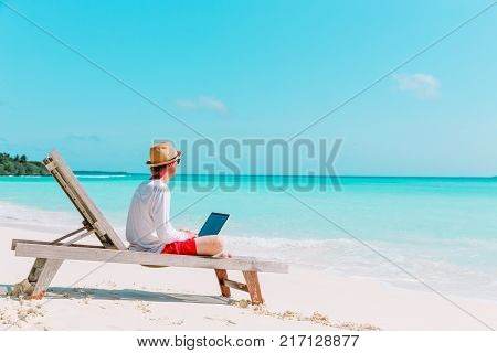 young man working on laptop at tropical beach, remote work concept