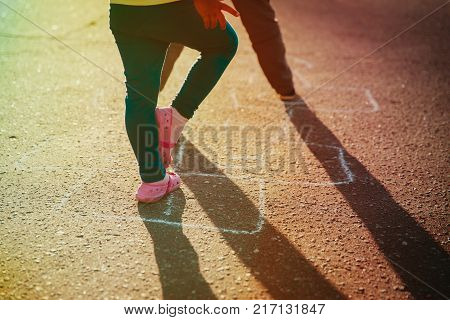 kids playing hopscotch on playground outdoors, kids outdoor activities