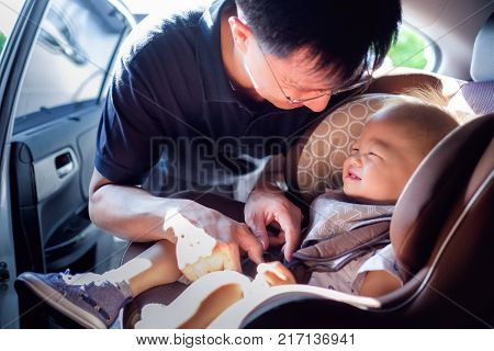 Smiling Middle age asian father helps his cute little asian 1 year old toddler baby boy child to fasten belt on car seat in car before driving happy traveling with child concept