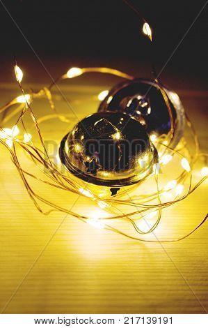 Two jingle bells and christmas chain/Two jingle bells and christmas chain with yellow light.