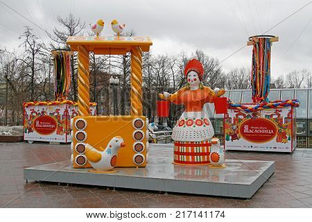 Moscow Russia - February 27 2017: Traditional Dymkovo toy woman with a yoke and buckets near well and birds as art object at Russian national festival