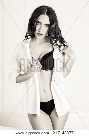 Hot brunette in a man's white shirt on a white background. Sexy young woman with a weary look in black lingerie and shirt. Monochrome