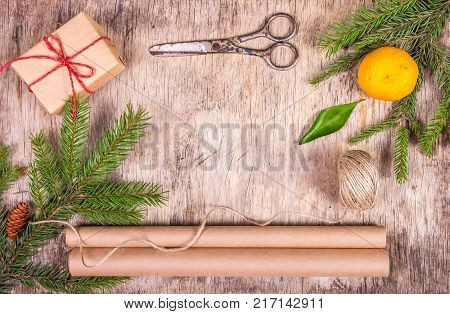 Christmas decorations with fir tree gift box packing paper tangerine and old scissors. Preparation for Christmas and gift wrapping.