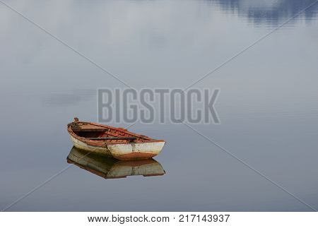 Wooden boat reflected in the still waters of a sea loch at Puyuhuapi, a small town on the Carretera Austral in northern Patagonia, Chile