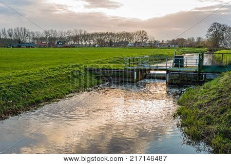 Backlit image of a Dutch polder in the fall season. The small weir regulates the water level in the ditch.