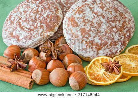 Gingerbread with haselnuts and spices on green background