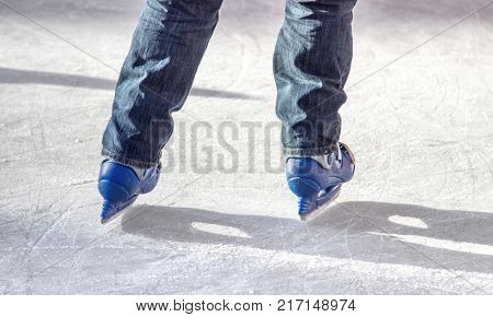 legs of a skater with blue skates on ice