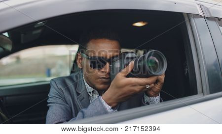 African american paparazzi man sitting inside car and photographing with slr camera poster