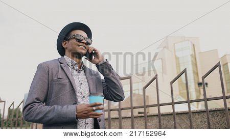 African mafia man in suit and sunglasses talking phone and walking down the street outdoors