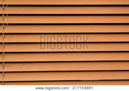 Close up image of window covered with beige horizontal blinds