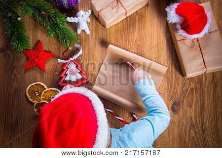 Top view of child writing letter to Santa Claus for Christmas