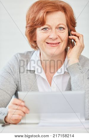 Senior business woman with competence and experience calling with smartphone