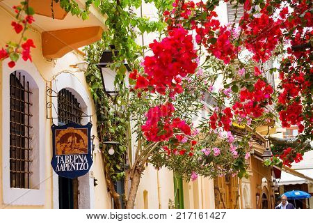Rethymno Greece - May 3 2016: Decorated street advertising signboard on narrow touristic street in tourist routes. Walk around old resort town Rethymno in Greece. Mediterranean architecture on Crete