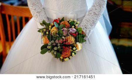 Wedding bouquet in the hands of the bride. The bride is holding a bouquet of flowers in front of her.
