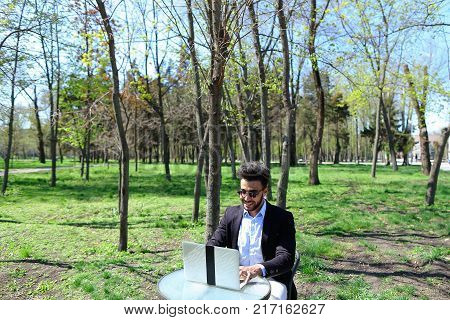 Author uses laptop and clicking buttons on keyboard. Smiling man has short dark hair, beard and dimples on face. Writer wears sunglasses, blue shirt and black jacket. Concept of modern technologies good working conditions apps for writing on laptop.
