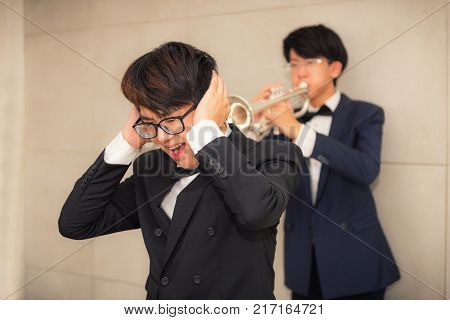 Portrait of young man playing trumpet to loudly sound and annoying his friend.