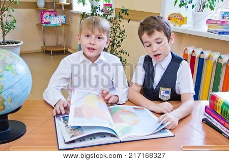 Two small schoolboys sitting together at table in class, reading the study book looking at camera - Russia Moscow first high school 2 class b - October 28 2017