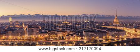Turin Italy: cityscape at sunrise with details of the Mole Antonelliana of Torino towering over the city. Scenic colorful light on the snowcapped Alps in the background. Panoramic view
