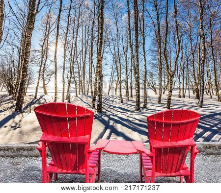 Bright winter frosty day. Large and comfortable red plastic chaise lounges for relaxing. Sunset in the Arctic. The concept of extreme and ecotourism tourism
