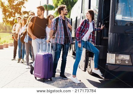 A group of tourists preparing to get on the bus. The guy with the girl goes into the bus and brings in their luggage. The girl goes first. Behind them is a group of tourists who are waiting.