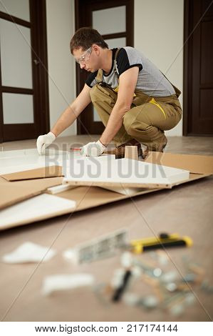 Carpenter man assembling furniture in house. Assemble furniture theme