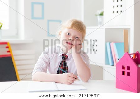 A first grader is sitting at a desk