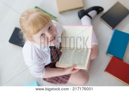 First-grader is sitting on the floor with books