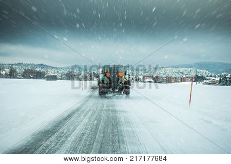 Winter Service Truck Or Gritter Spreading Salt On The Road Surface To Prevent Icing In Stormy Snow W
