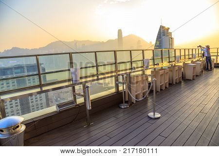 Hong Kong, China - January 1, 2016: travel photographer takes a pictures of Victoria Harbor Skyline at sunset from the rooftop of Eye Bar, inside iSquare shopping center on Nathan Road, Tsim Sha Tsui.