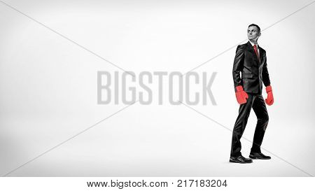 A businessman stands in half turn on a while background wearing a suit and red boxing gloves. Business and success. Ready for risk. Competition for profit.