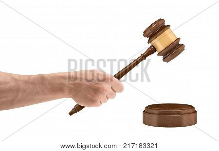 A large male hand holds a wooden judge gavel above a round sound block isolated on a white background. Legal action. Bring to court. Business and law.