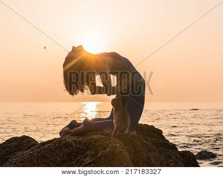 Young Woman in Bodysuit Practicing Yoga With Gray Cat on the Beach Near the Sea at Amazing Sunrise.