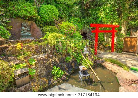 Kamakura, Japan - April 23, 2017: Japanese bamboo fountain in Hase-Dera garden or Hase-kannon and Torii gate or Shinto gate in front of Benten-kutsu cave entrance. Hasedera Temple is popular landmark