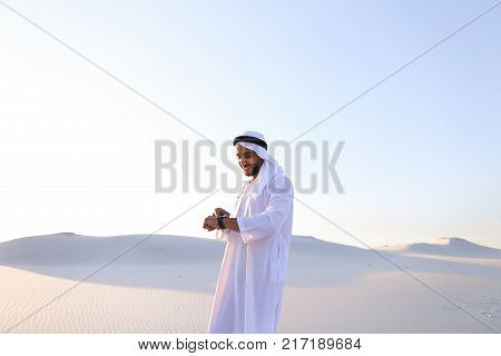 Attractive guy, emirate businessman uses for business and for work Watch, who are put on hand, smiling and examining landscapes of large sandy desert against blue sky on hot summer morning. Swarthy Muslim with short dark hair dressed in kandura
