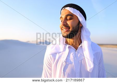 Close-up portrait of handsome Muslim young man who smiles and looks around, watching beauty of nature in sandy desert with white sand against blue sky in national suit that develops in wind. Swarthy Muslim with short dark hair dressed in kandura, long, sp