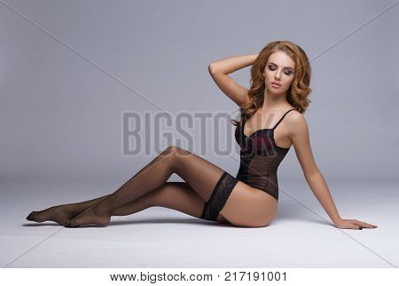 Young, seductive and beautiful girl in erotic lingerie posing in studio. Woman in sexy underwear.