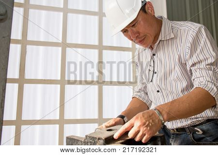 Professional Asian engineering wearing safety helmet performing quality checking production on a factory