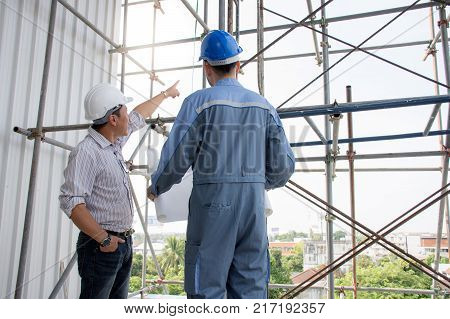Professional Asian engineering team wearing safety helmet talking about construction project and pointing finger up at construction site