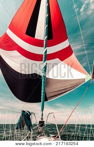 Spinnaker with uphaul on sail boat blue sky in background. Marine sailing objects concept.