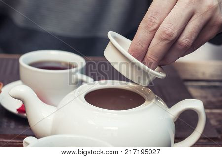 Opening a chinese white teapot shows the lifestyle in slow and ease. Clear brain with wisdom and open mind. Friends enjoy the peaceful moment.