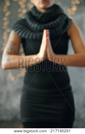 Smiling woman in sportswear practicing yoga standing in Vrksasana exercise with namaste Tree pose on gray background and bokhee