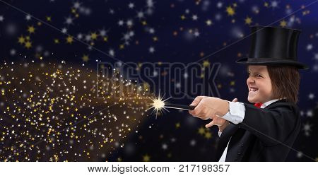 Magician boy with hardhat pointing to copy space with magic wand and making funny grimace with a grin