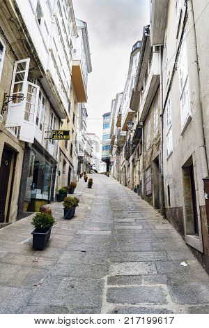 Betanzos Galicia / Spain-August 25 2017: Very steep street with stone floors with flower pots and small shops