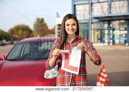 Happy young woman tearing learner driver sign near car