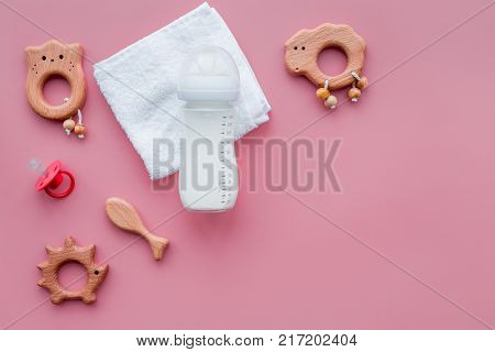 Little baby background. Wooden toys, pacifier, bottle, towel on pink background top view.