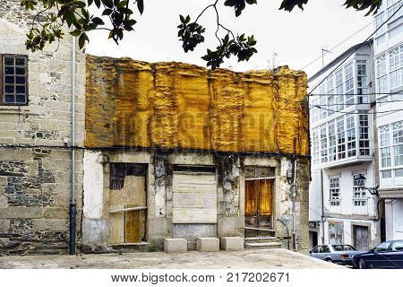 Ruined house with yellow thermal insulation in sight and doors locked with wood