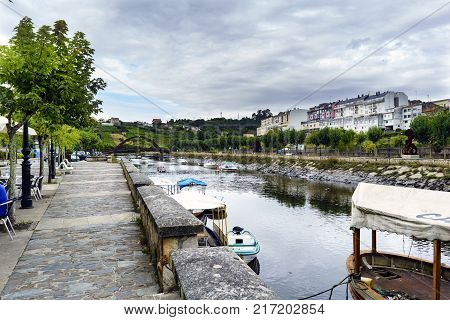 View of the Betanzos river from one of the banks with small boats moored and an iron bridge in the background