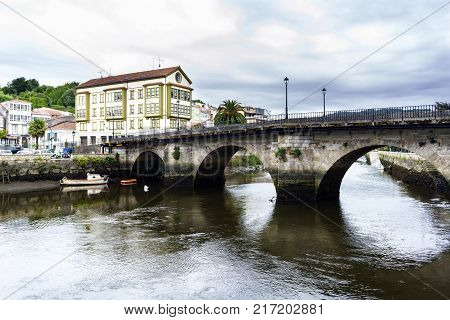 Roman bridge over the Ria de Betanzos with a strong current and in the middle of a town in Galicia Spain