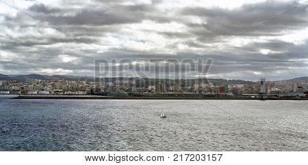 Panoramic view of the city of La Coruna on the Atlantic coast of Galicia (Spain). Sky with dark clouds and sun reflections