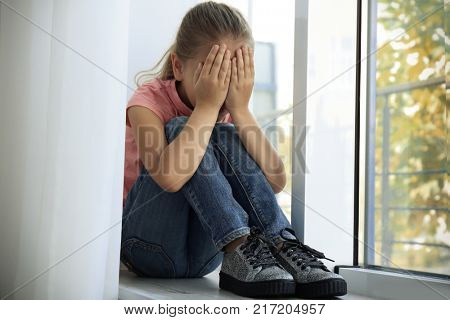 Little sad girl crying at home. Abuse of children concept